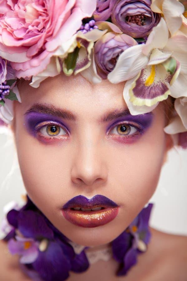 Verticale foto van het charmeren van jonge vrouw met bloemen op hoofd stock foto