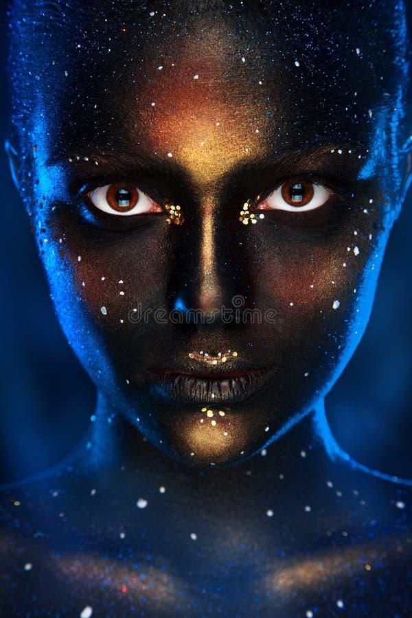 Verticale foto van mooie vrouw met zwart gezichtsart. stock foto