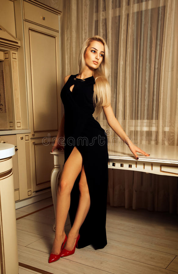 Verticale foto van seksuele schoonheidsvrouw in lang zwart kleding en Re royalty-vrije stock foto's