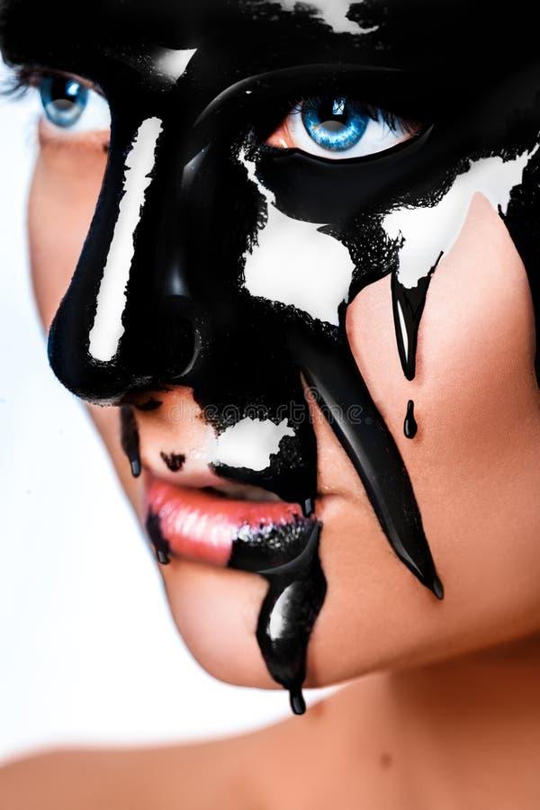 Verticale foto van sexy vrouw met zwarte verf op gezicht stock foto