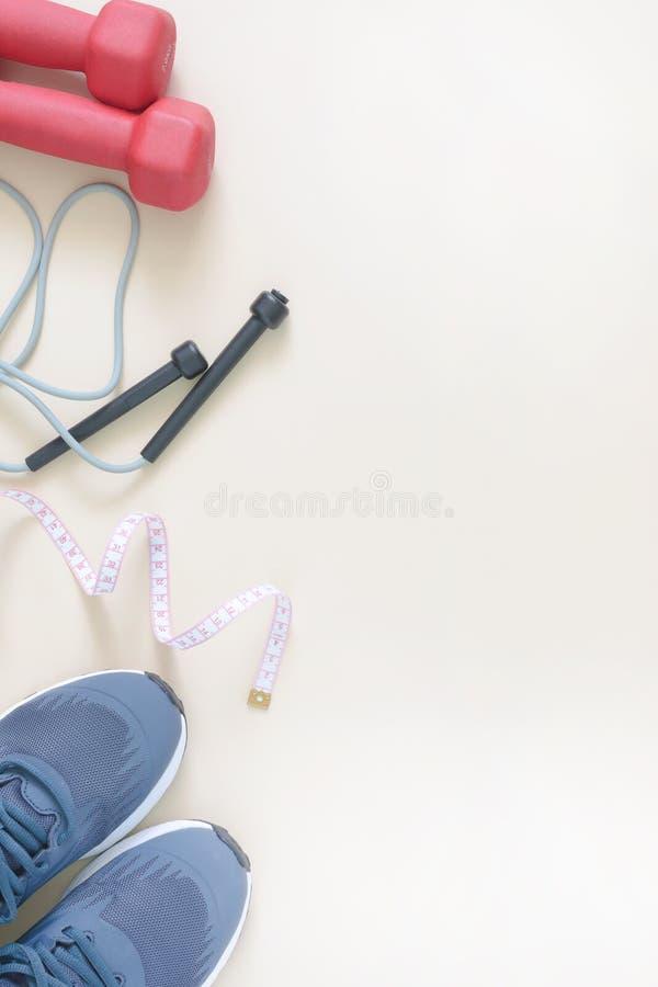 Verticale Geschiktheidsachtergrond Op de rand lig sportenschoenen, een touwtjespringen en een centimeterband Plaats voor tekst stock foto