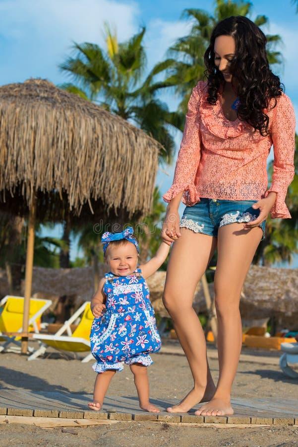 Verticale heureuse de mère et de descendant Vacances de famille par la mer Apprenez à marcher images libres de droits