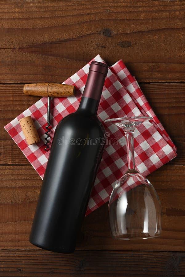 Verticale Hoge hoekmening van een rode wijnfles op een rood en wit geruit servet royalty-vrije stock afbeeldingen
