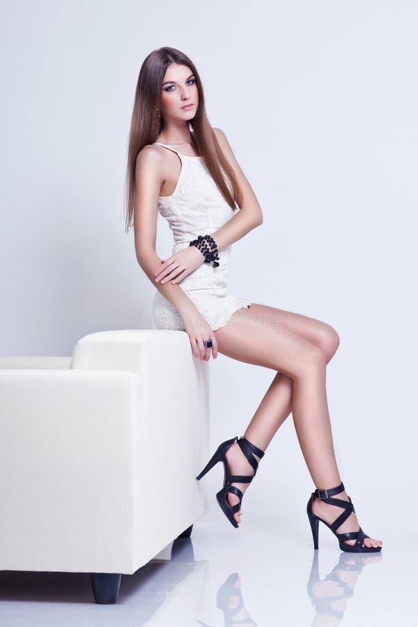 Verticale intégrale de belle jeune femme de brune sur le divan photo libre de droits