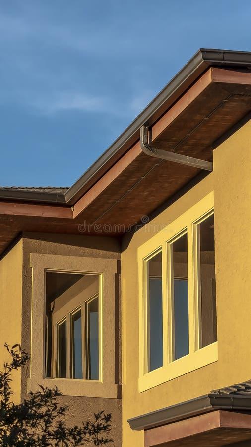 Verticale kader Dichte omhooggaand van een huis hogere verdieping buiten met bomen en blauwe hemel op een zonnige dag royalty-vrije stock afbeeldingen