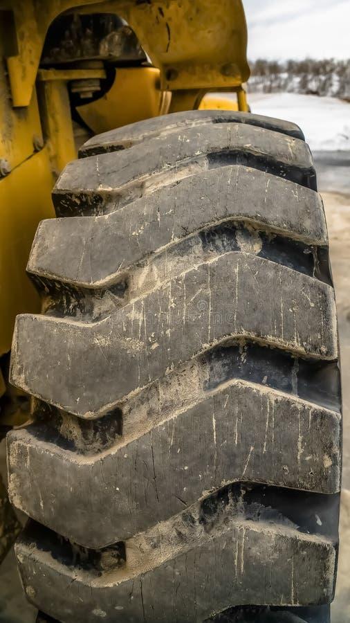 Verticale kader Dichte omhooggaand van zwart rubberwiel met diagonaal loopvlak van een bouwvoertuig stock foto's