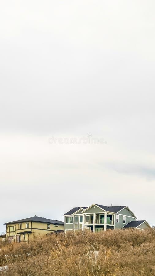 Verticale kader Heldere bewolkte hemel over huis met meerdere verdiepingen die op berg met sneeuw in de winter wordt behandeld royalty-vrije stock foto's