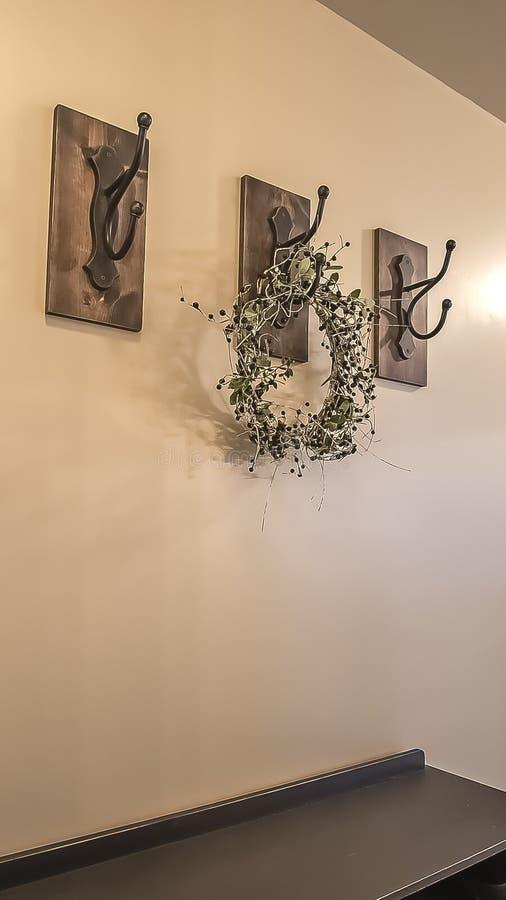 Verticale kader Houten kabinetten en ijzerhaken tegen de beige muur van een huis met witte vloer royalty-vrije stock afbeeldingen