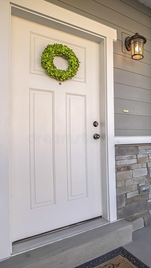 Verticale kadervoorgevel van een huis met een eenvoudige kroon die op de witte houten deur hangen royalty-vrije stock fotografie