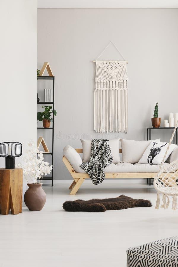 Verticale mening van comfortabele woonkamer met modieuze laag met hoofdkussens, bonttapijt en wit macramé op de muur royalty-vrije stock fotografie