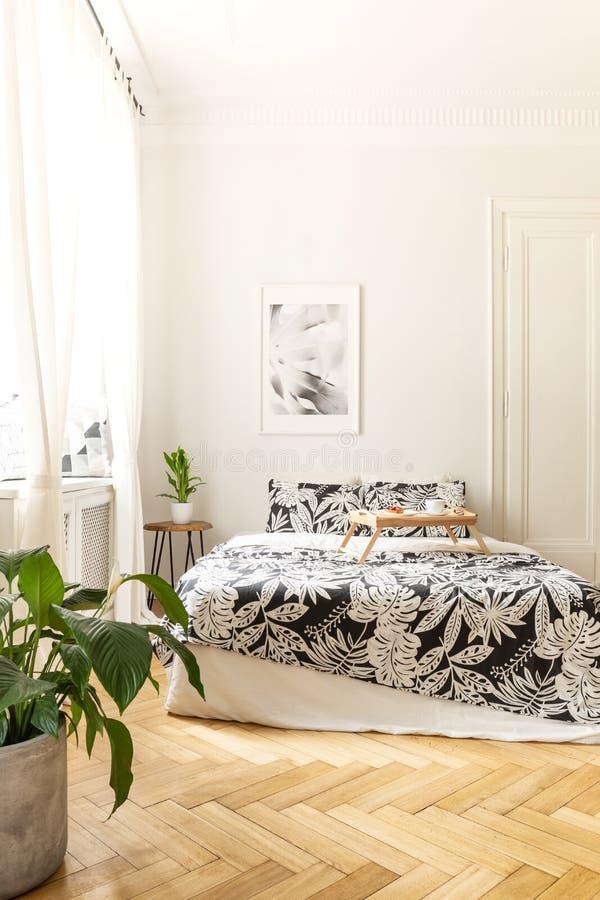 Verticale mening van een helder slaapkamerbinnenland met een groot bed die zich op een visgraat houten vloer bevinden Zwart-wit b royalty-vrije stock foto