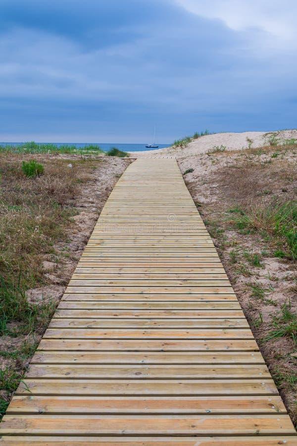 Verticale mening van houten weg naar het strand met overzees en bewolkte hemel op de achtergrond royalty-vrije stock afbeelding
