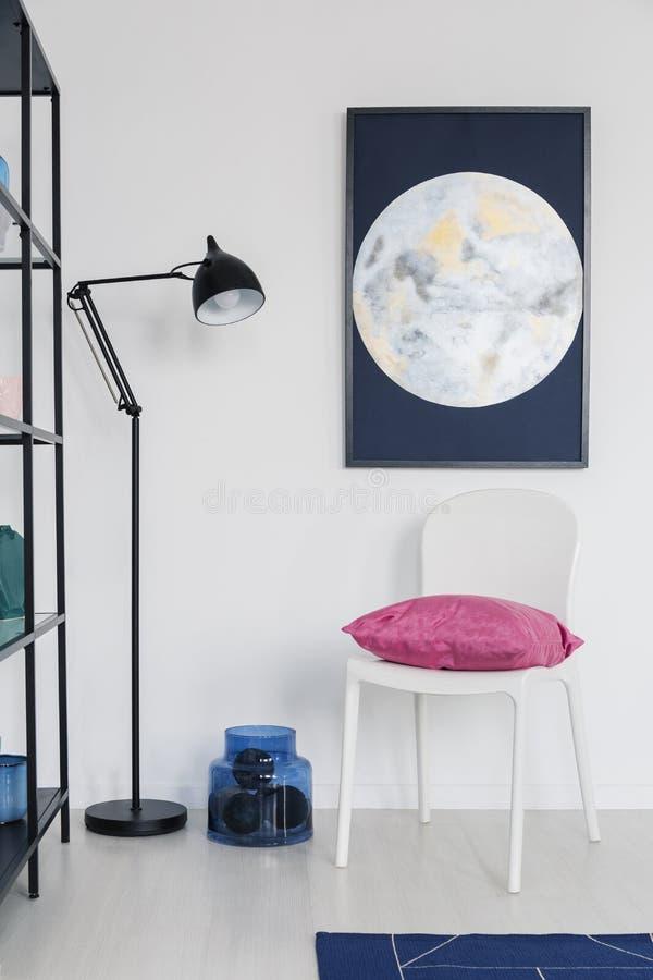 Verticale mening van witte stoel met roze hoofdkussen in wit binnenland met maan grafisch op de muur en metaallamp, echte foto stock afbeelding