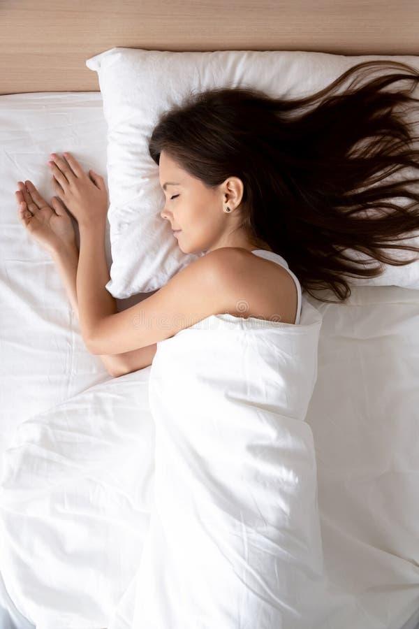 Verticale, mooie jonge vrouwenslaap in comfortabel bed stock fotografie