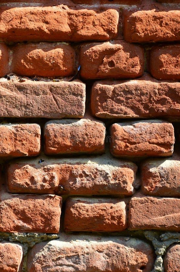 Verticale muurtextuur van verscheidene rijen van zeer oud die metselwerk van rode baksteen worden gemaakt Verbrijzelde en beschad stock afbeelding