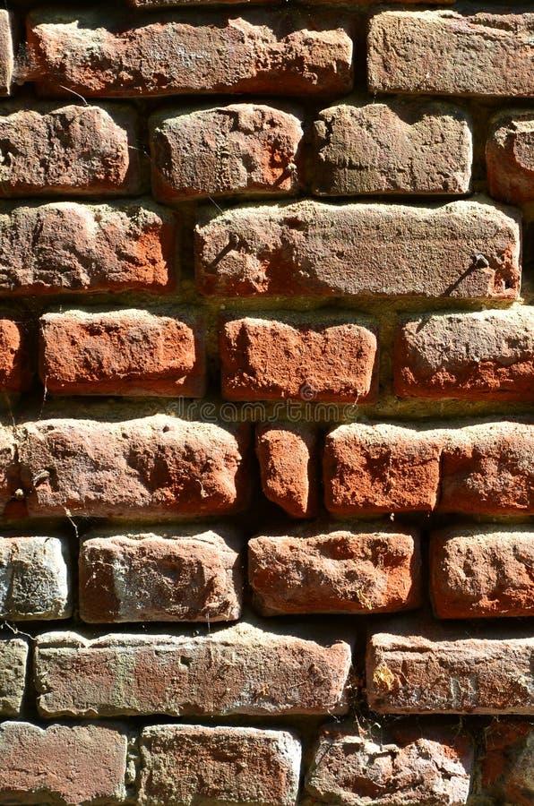 Verticale muurtextuur van verscheidene rijen van zeer oud die metselwerk van rode baksteen worden gemaakt Verbrijzelde en beschad stock afbeeldingen