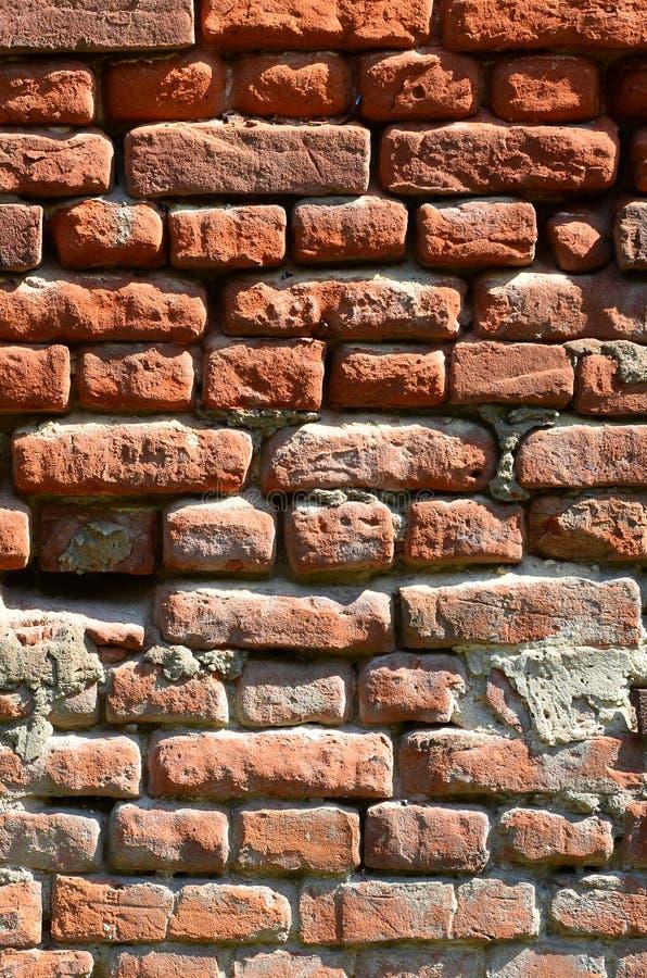 Verticale muurtextuur van verscheidene rijen van zeer oud die metselwerk van rode baksteen worden gemaakt Verbrijzelde en beschad royalty-vrije stock foto