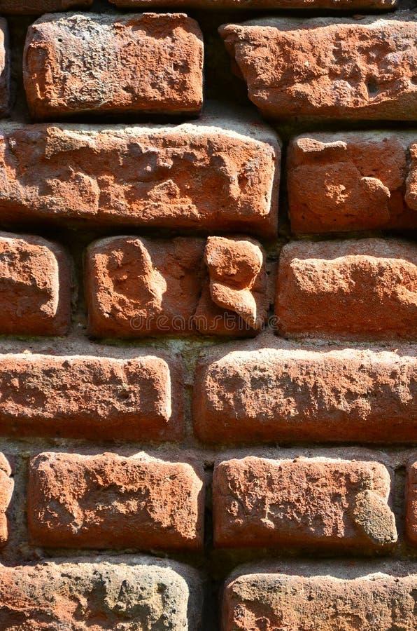 Verticale muurtextuur van verscheidene rijen van zeer oud die metselwerk van rode baksteen worden gemaakt Verbrijzelde en beschad stock foto's