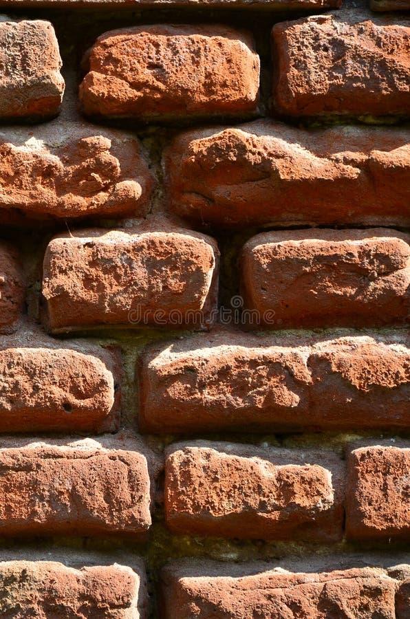 Verticale muurtextuur van verscheidene rijen van zeer oud die metselwerk van rode baksteen worden gemaakt Verbrijzelde en beschad stock fotografie