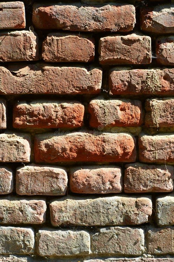 Verticale muurtextuur van verscheidene rijen van zeer oud die metselwerk van rode baksteen worden gemaakt Verbrijzelde en beschad stock foto