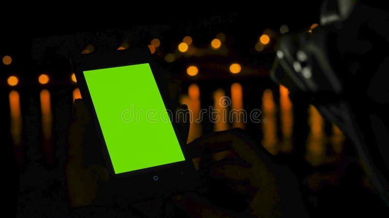 Verticale smartphone van het vrouwengebruik met het groene scherm op dek van cruiseschip bij nacht stock fotografie