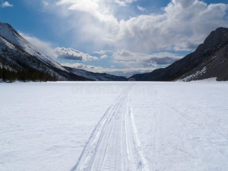 Vertiefung benutzte Winterspur auf gefrorenem Gebirgssee stockbilder