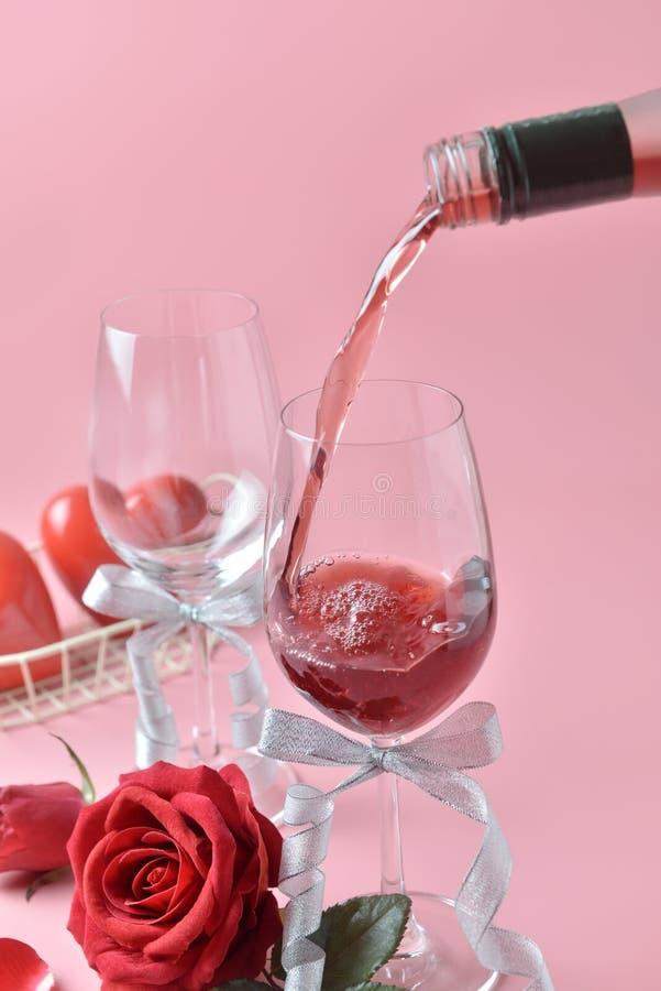 Vertiendo fuera del vino tinto de la botella al vidrio, con la rosa en la parte inferior en fondo rosado Concepto de día del ` s  foto de archivo libre de regalías