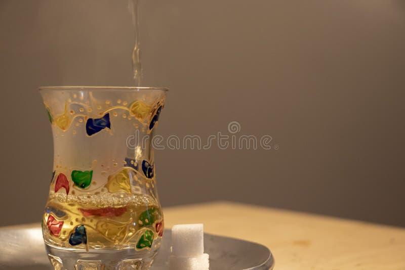 Vertiendo un vidrio de cocer té de la menta al vapor fotografía de archivo libre de regalías