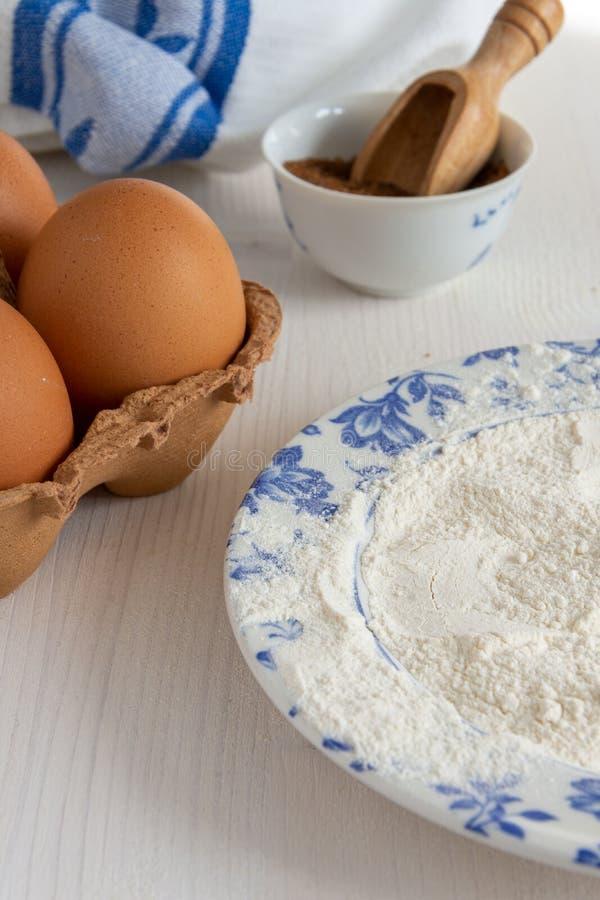 Vertikal bästa sikt av ingredienser för bakelser, farin och mjöl i blå maträtt royaltyfria bilder