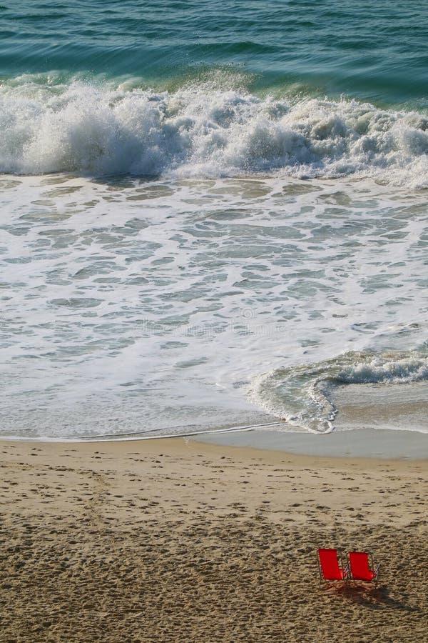 Vertikal bild av de krascha vågorna i havet med röda strandstolar på den sandiga stranden royaltyfria bilder