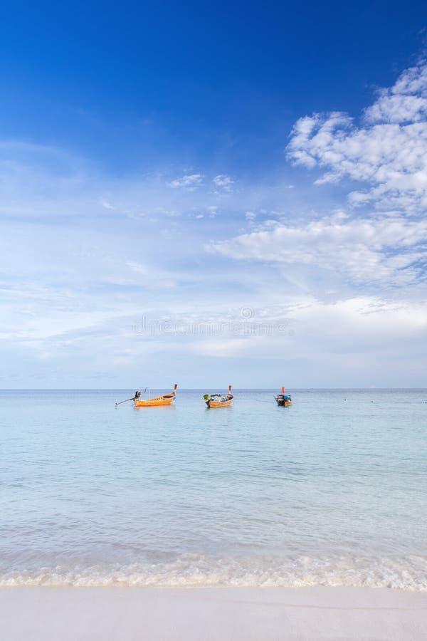 Vertikal bild av det träthailändska traditionella longtailfartyget på den vita sandstranden på den Lipe ön, Satun, Thailand royaltyfri foto