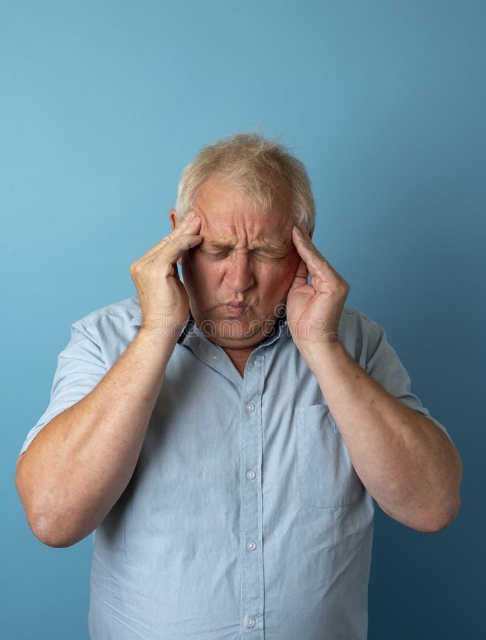 Vertikal bild av en mogen man med en huvudvärk arkivfoto