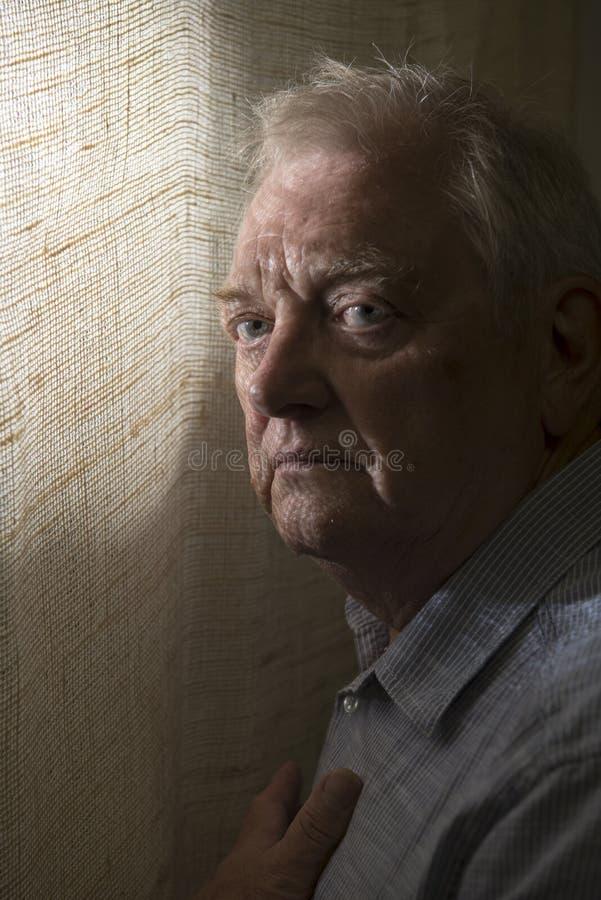 Vertikal bild av en mogen man med skuggor på hans framsida arkivfoton