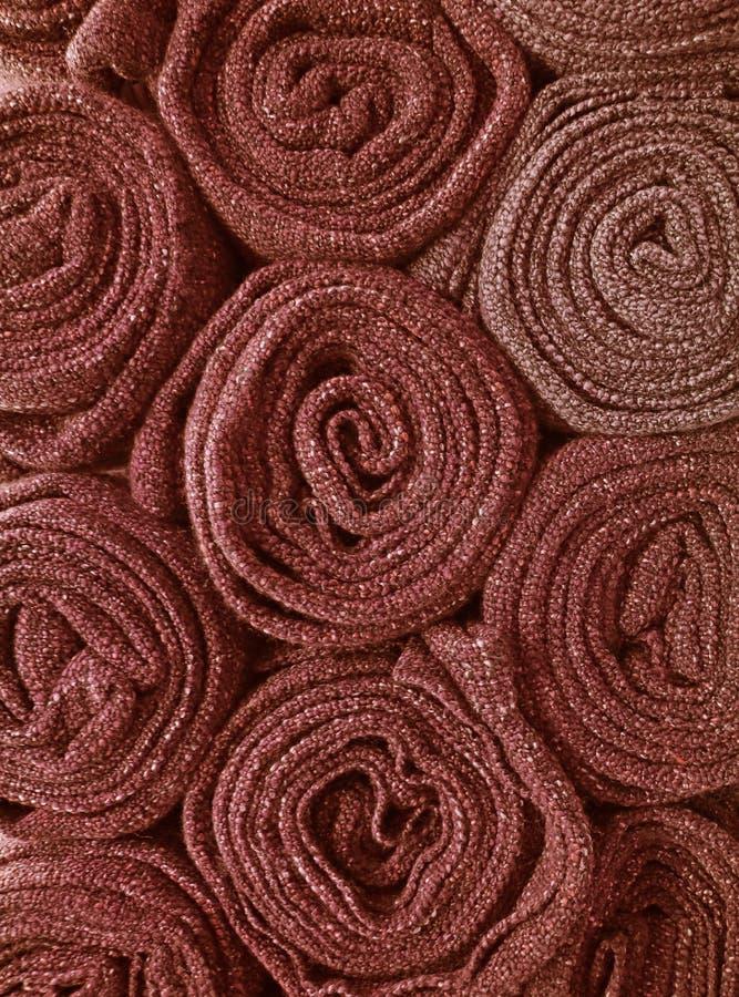 Vertikal bild av högen av hoprullade röda bruna filtar för bakgrund royaltyfri foto