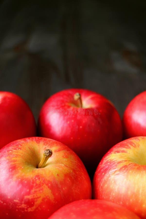 Vertikal bild av högen av nya mogna röda äpplen som isoleras på trätabellen för mörk färg med kopieringsutrymme arkivbild