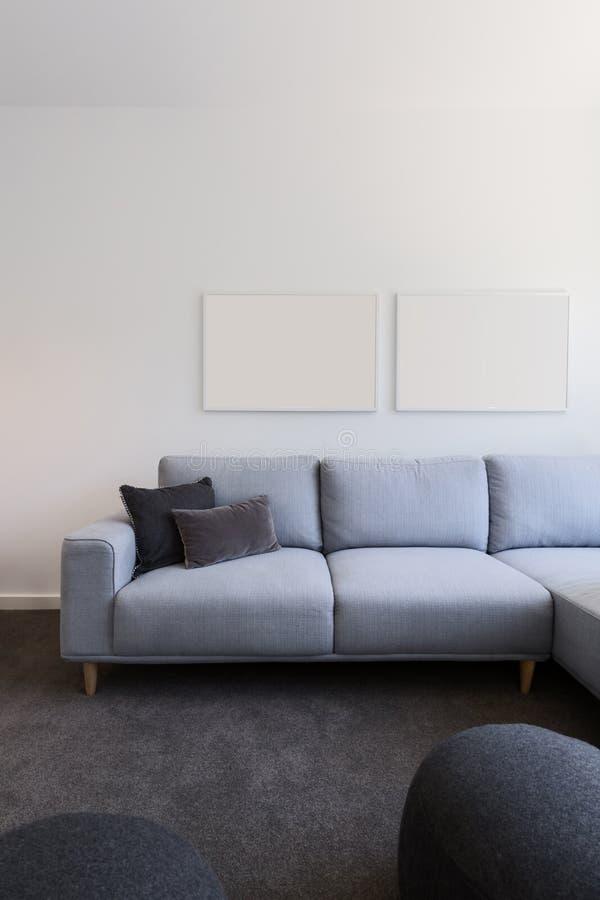 Vertikal bild av pastellblåttsoffan med tomt konstverk över arkivbild