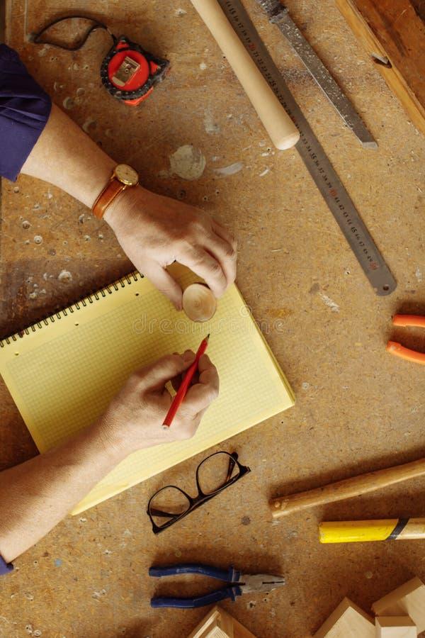 Vertikal bild för bästa sikt av manhänder på skrivbordet för carpener` s med funktionsdugliga hjälpmedel royaltyfri fotografi