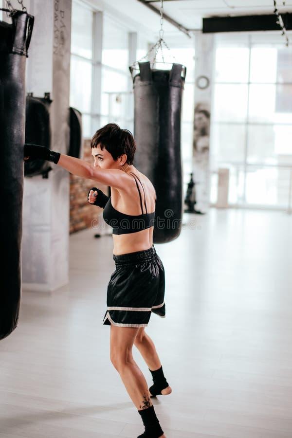 Vertikal bild för sidosikt av det kvinnliga deltagandet för passform i boxningsporthändelse fotografering för bildbyråer