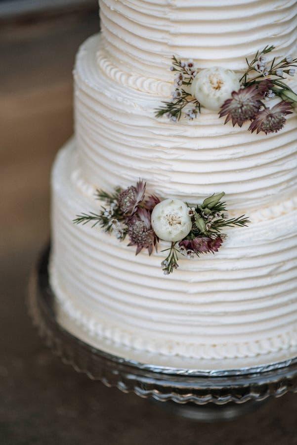 Vertikal closeup som skjutas av en dekorerad tre-lager bröllopstårta med blommor på ett silveruppläggningsfat arkivfoto