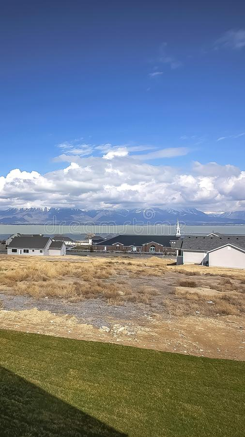 Vertikal grannskap med sikt av sjön och berget under molnig blå himmel på en solig dag royaltyfria bilder