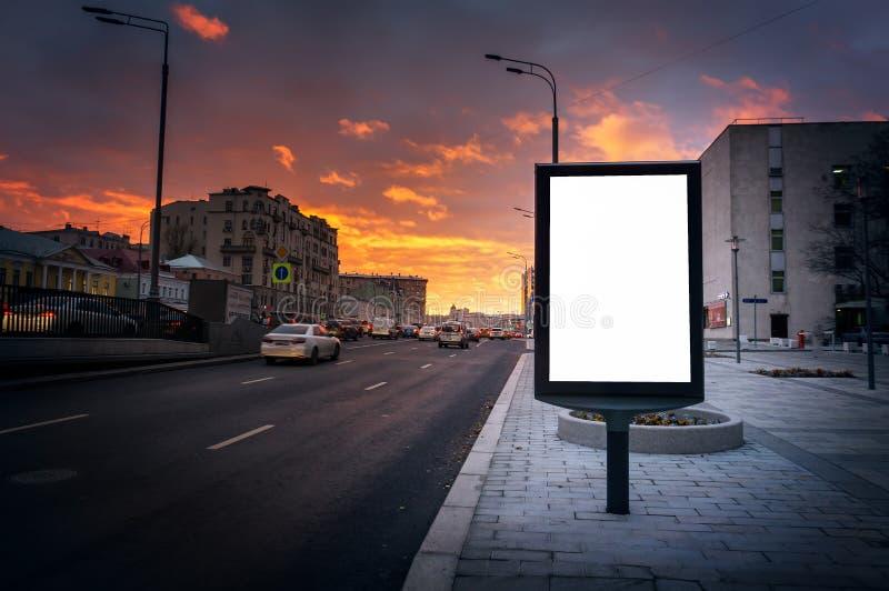 Vertikal ljus ask, affischtavlaplatta på bakgrunden av en väg på natten i solnedgången, fritt utrymme för designen, åtlöje upp royaltyfria bilder