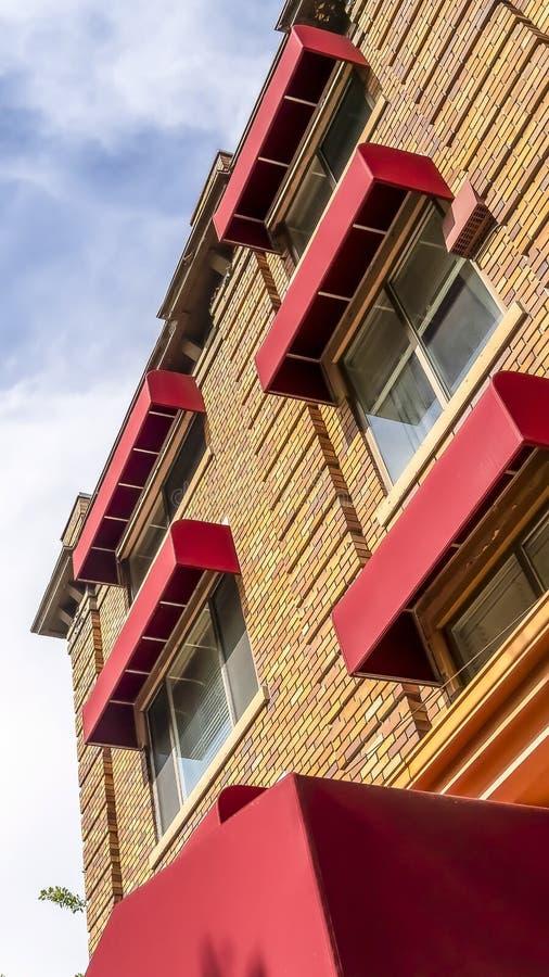 Vertikal rambyggnad med den gula väggen för stentegelstenyttersida och röda markiser på fönstren royaltyfria bilder