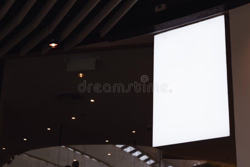Vertikal signagemodell för tom vit skärm som hänger på tak skylt f?r annonseringdesignen i en k?pcentrum, galleri royaltyfria bilder