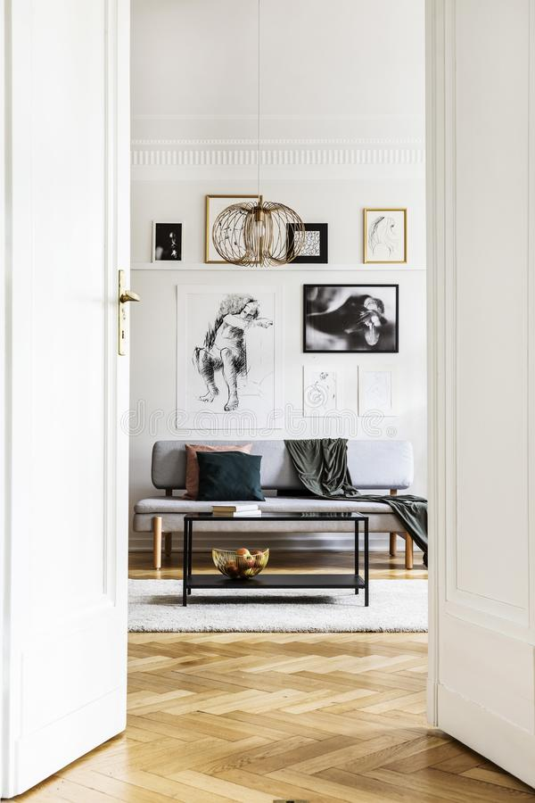 Vertikal sikt av den öppna dörren till vardagsrum som är inre med den gråa soffan, den industriella kaffetabellen och den guld- l royaltyfria foton