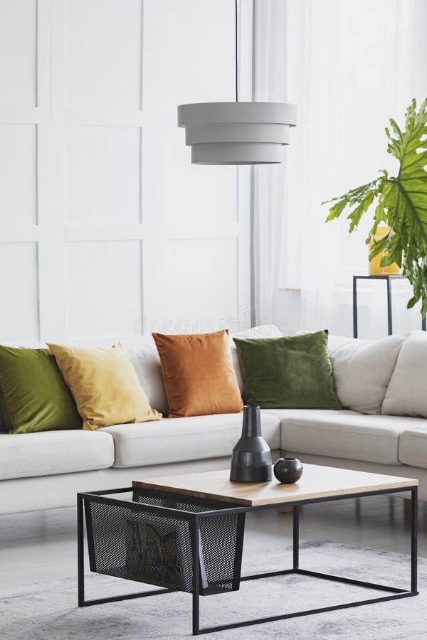 Vertikal sikt av den enkla vita ljuskronan som hänger ovanför den moderna träkaffetabellen i vardagsrum med guld- limefruktbrytni royaltyfri bild