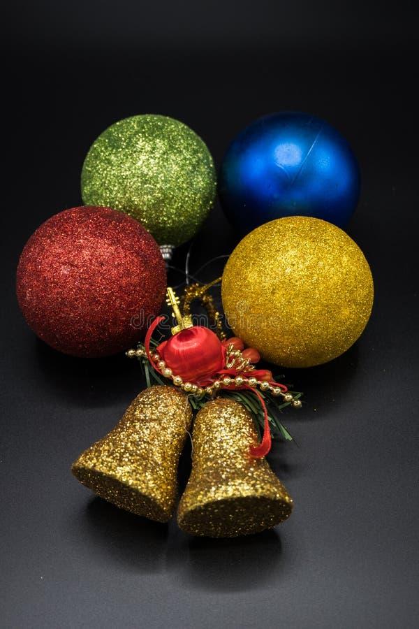 Vertikal sikt av den guld- klockan och färgrika julbollar på svart bakgrund royaltyfri foto