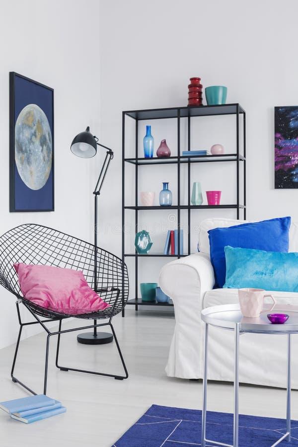 Vertikal sikt av den stilfulla fåtöljen med den rosa kudden i modern vardagsrum som är inre med det vita diagrammet för soffand-m fotografering för bildbyråer
