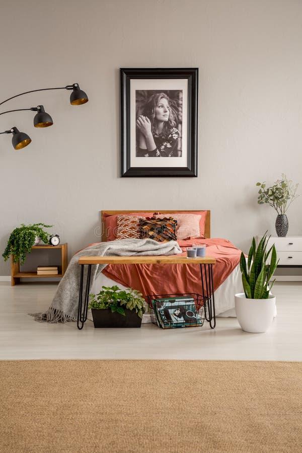 Vertikal sikt av det stilfulla sovrummet med konungformatsäng med kulör sängkläder för rost, affischen på väggen och den gröna vä arkivbilder
