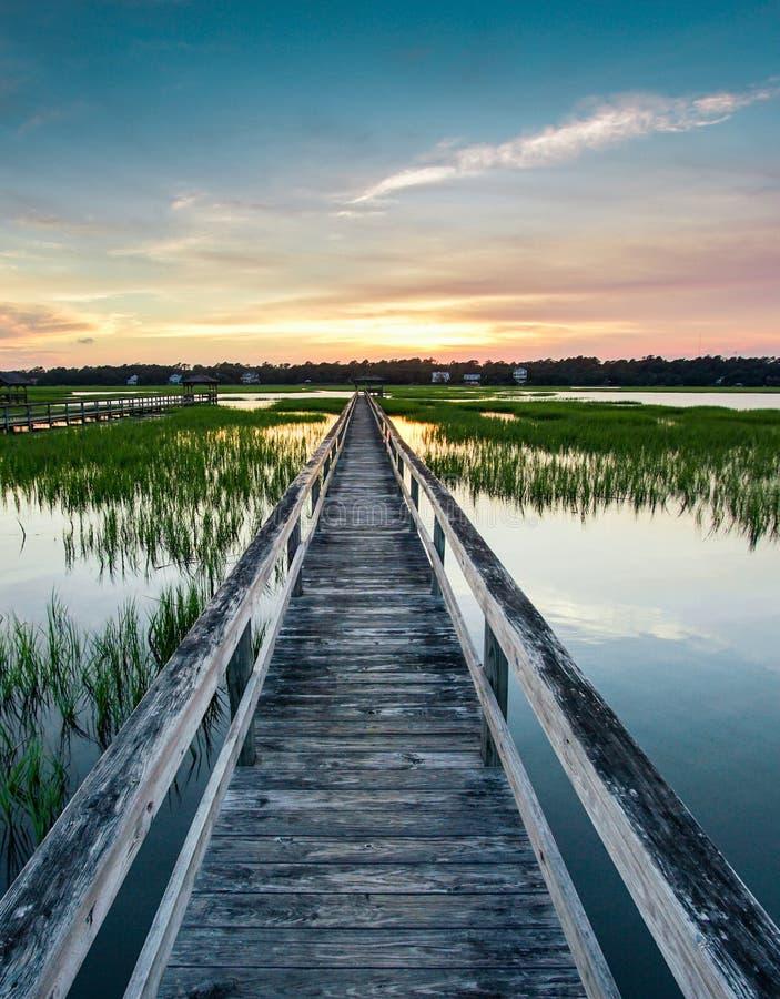 Vertikal sikt av en härlig solnedgång över kust- vatten med en mycket lång trästrandpromenadpir i mitten under en färgrik summa fotografering för bildbyråer