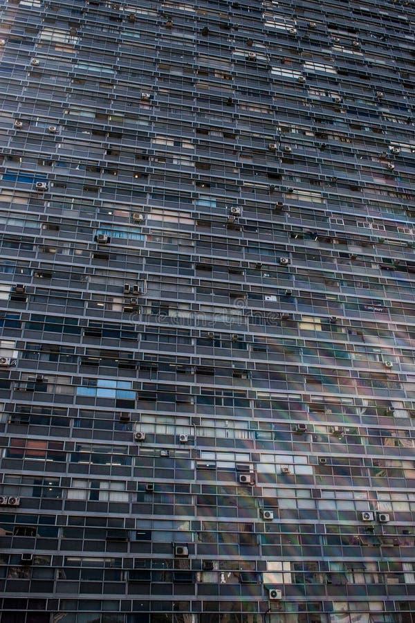 Vertikal sikt av en kontorsbyggnad med rektangulär glass windo arkivfoton